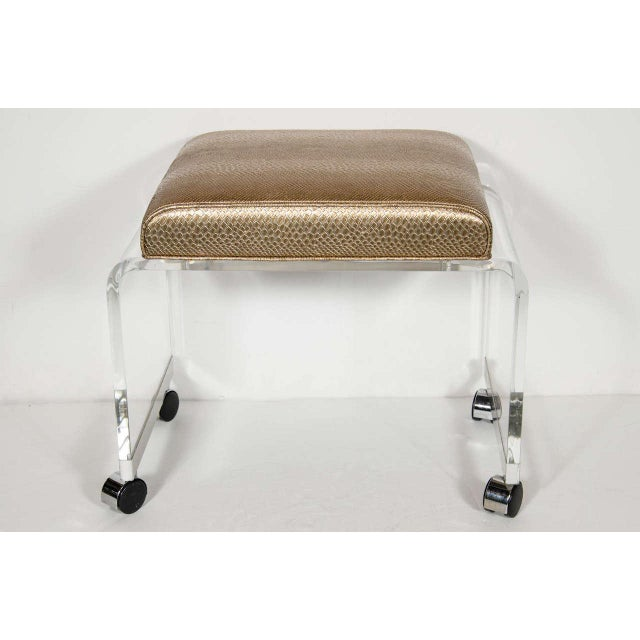 Chic Mid-Century Modernist clear Lucite bench or vanity stool in a waterfall design with chrome banding on the base that...