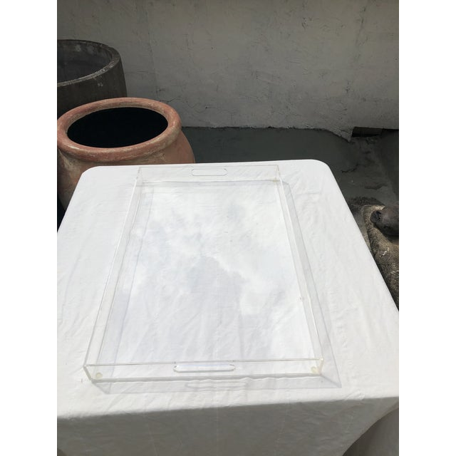 """This large lucite tray is the perfect modern addition to a bar to add a touch of sleekness. It measures 27.5"""" wide, 18..."""