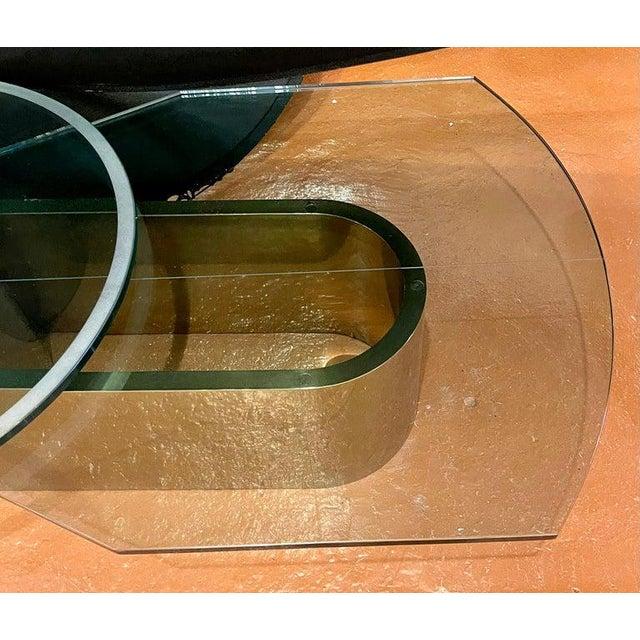 "Dakota Jackson self winding coffee table having two sculptural thick glass tops. The round glass: 36"" diameter the longer..."