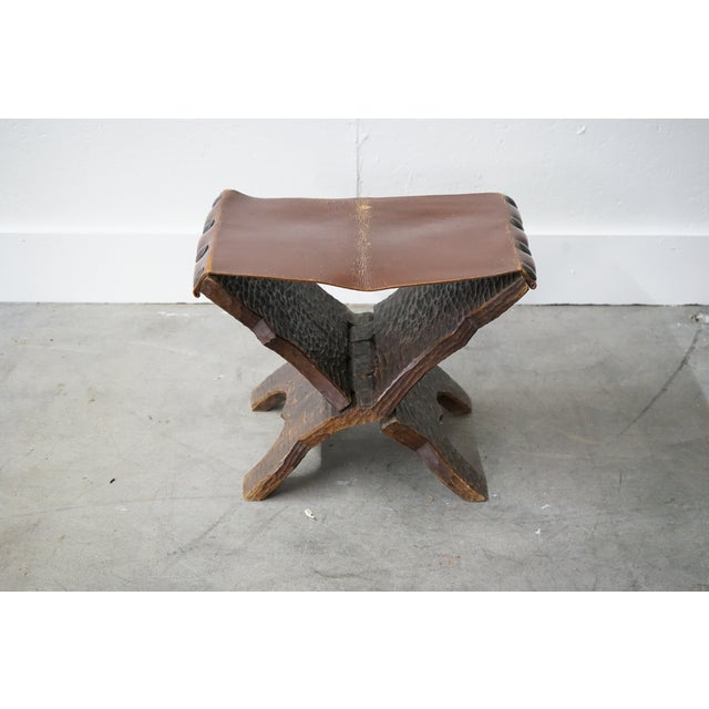 Look at this 1960s French, unique mid-century folding ottoman made of carved wooden planks with large oversized brass nail...