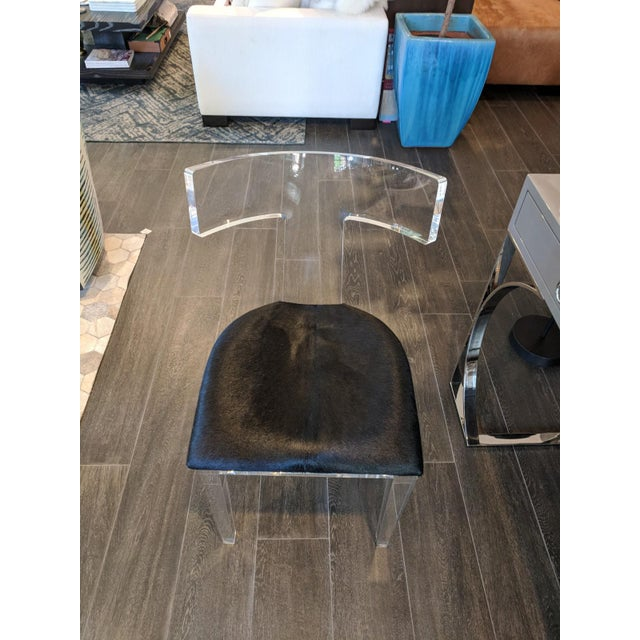 Solid lucite frame side chair with black cowhide seat. Curated by Plantation Design. Made in the 2010s