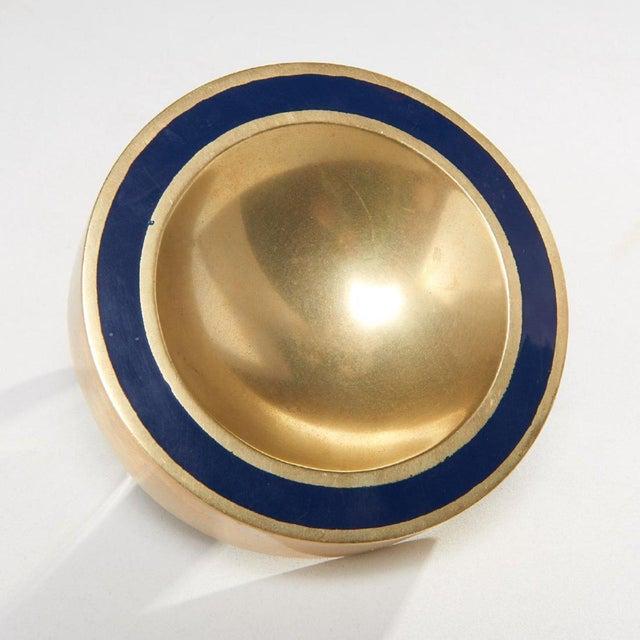 (2) Modernist brass vide poche, c. 1960s, round cast brass catch-all with blue enamel rim stripe, together with a...