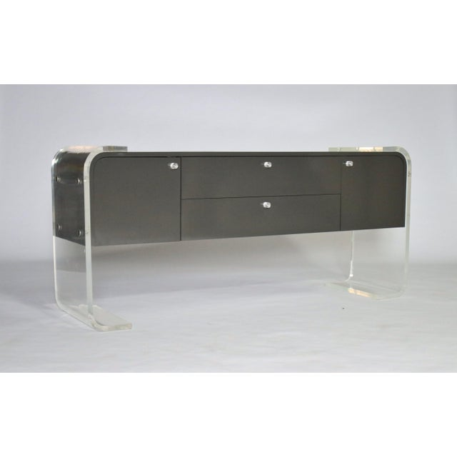 1970s lacquered charcoal gray wood buffet on a thick Lucite frame. Features two cabinets and two pull-out drawers with...