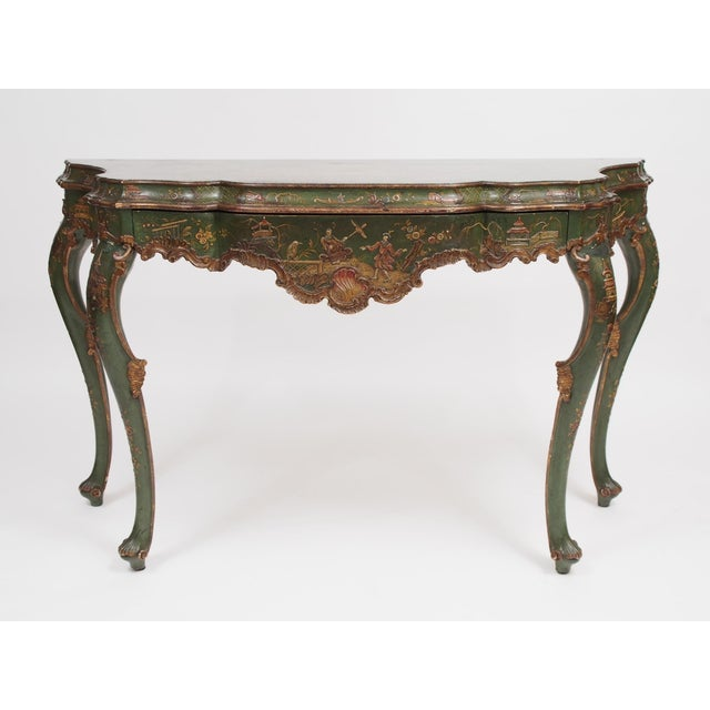 A polychrome Chinoiserie painted console table with a shaped top over a long drawer and deeply scalloped apron. The...