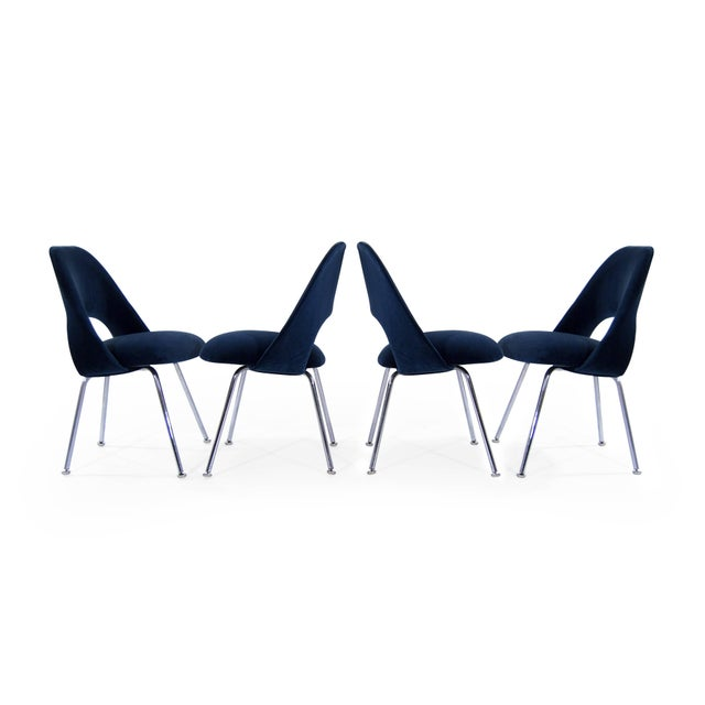 A set of four newly upholstered executive side chairs by Eero Saarinen, newly upholstered in navy velvet.