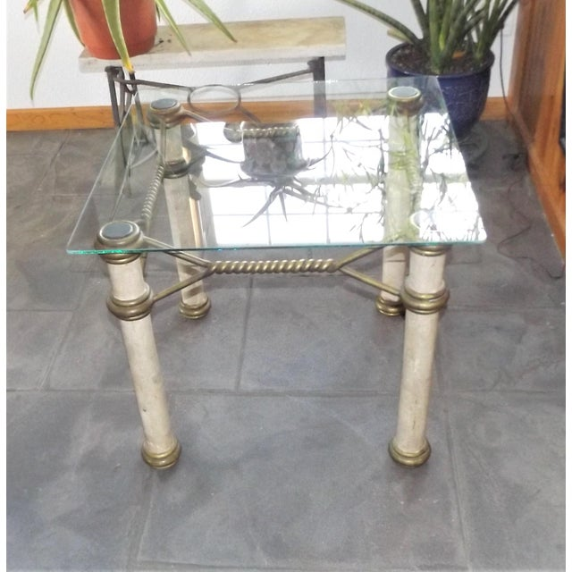Amazing Hollywood Regency style glass top coffee table. The legs are solid iron wrapped in faux marble and the trim is...