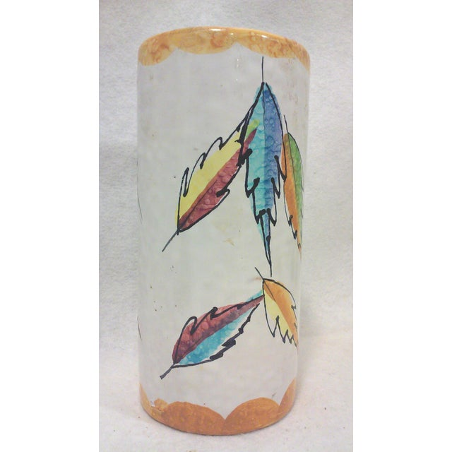 A vintage Italian ceramic cylindrical vase decorated with colorful abstract leaves and a scalloped orange border. This...