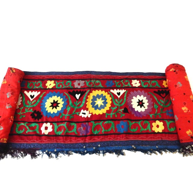 Superb vintage Suzani runner with tassels depicting traditional embroidery with a red background, creating a multitude of...