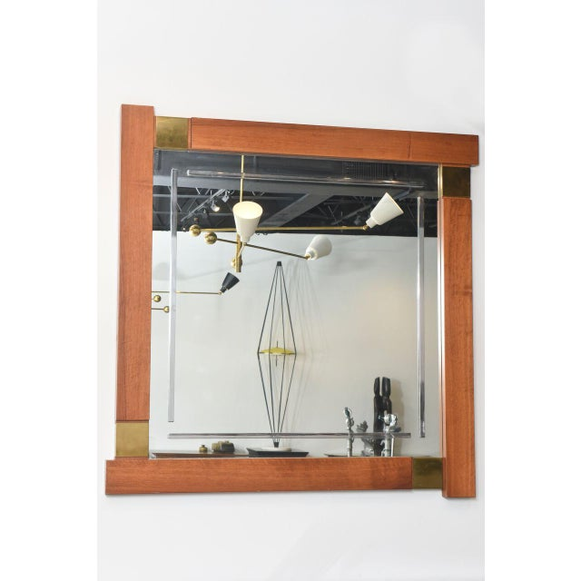 The wood frame with overhanging and stepped sides interrupted by brass lozenges, the central mirror frame with etched...