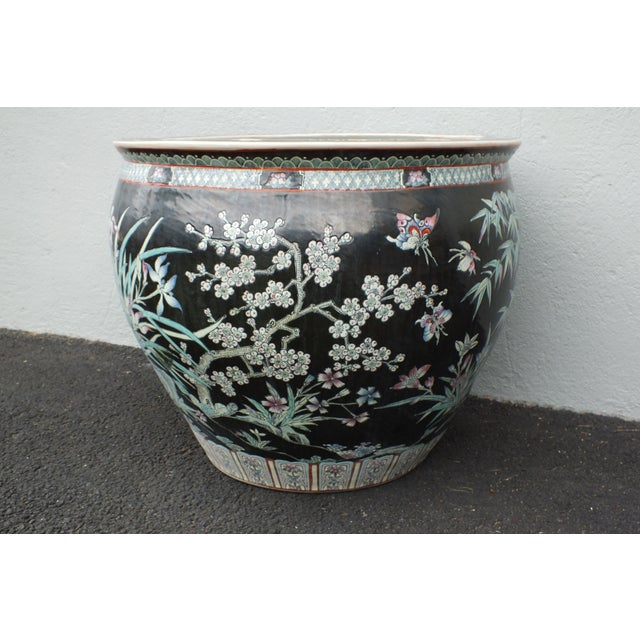 An extra large Chinese famille noir porcelain fish bowl planter. Features colorful hand painted raised images of lotus...