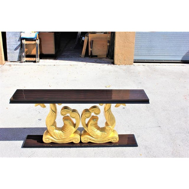 Unique long French Art Deco exotic Macassar ebony carved giltwood twin dolphin console table. Carved giltwood, original By...