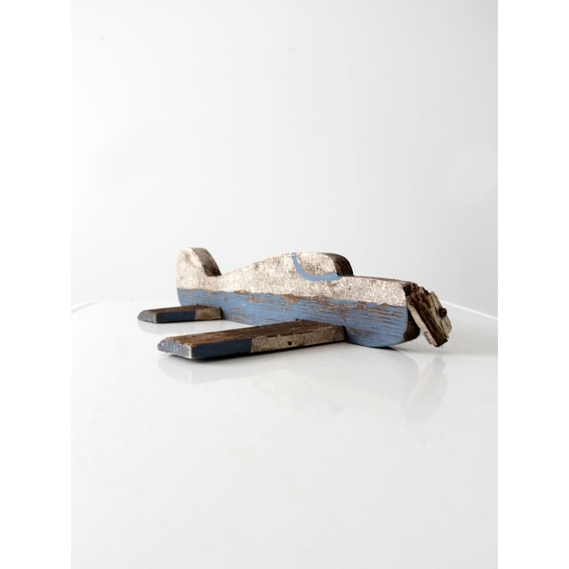Beautifully aged, this is a mid-century toy wood airplane. Worn white and blue paint color the carved wood plane. It...