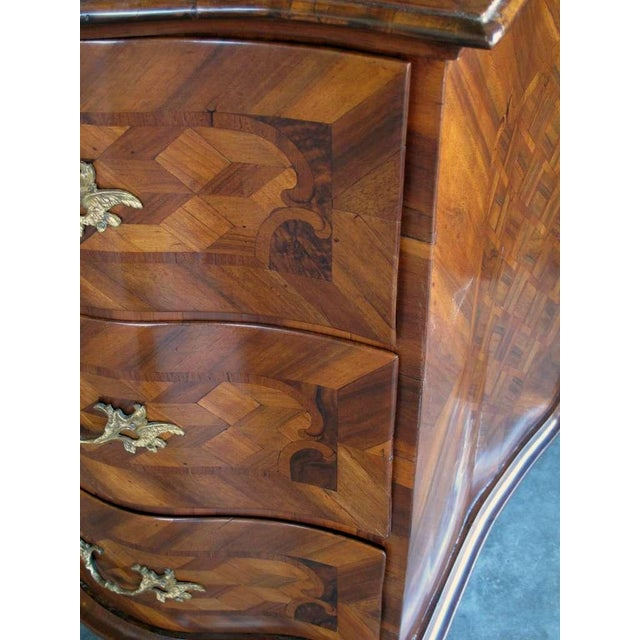 A handsome and good quality German baroque serpentine-form parquetry and walnut veneered 3-drawer chest; inlaid overall...
