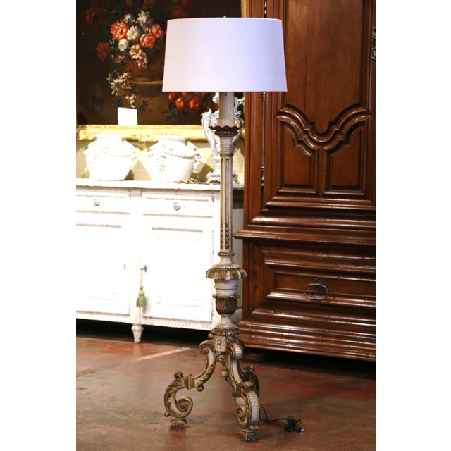 This tall antique wood floor lamp was carved in Italy, circa 1850. The elegant light stands a wide three-leg pedestal base...