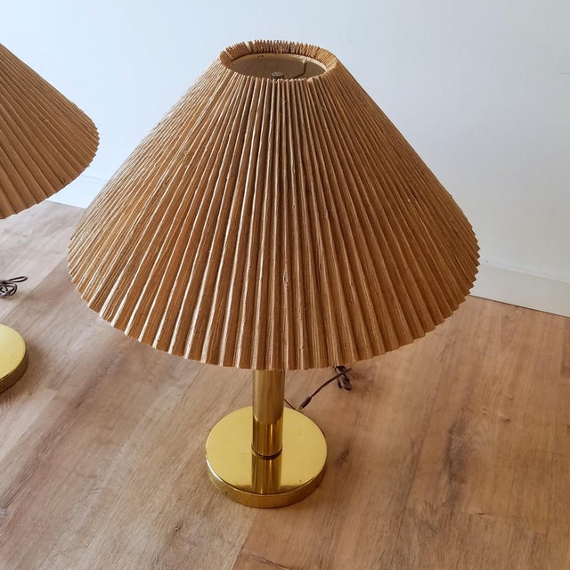 A pair of Mid-Century Modern brass table lamps with their original shades. There are two ball pulls, one to operate each...