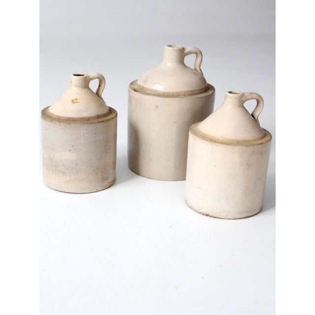 This is a set of three American stoneware jugs. These antique utilitarian crocks are beautiful statements in the kitchen...