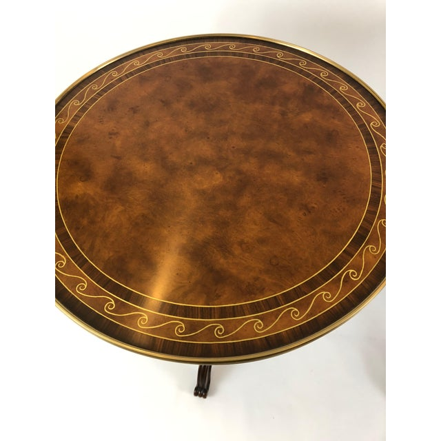 Two superb round side tables having burl and zebrawood inlaid tops with a gold neoclassical border and brass frame, carved...