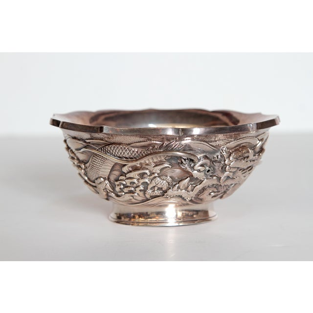 A Japanese silver bowl marked with highly decorative curving dragon in high relief around the body. Scalloped edge on top...