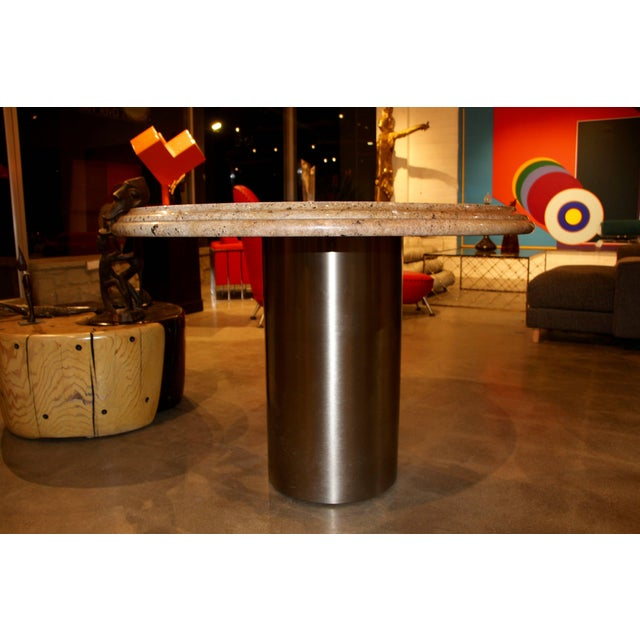 A nice centre table or dining table from the Pace Collection, with a brushed steel base and a granite top with a rounded...
