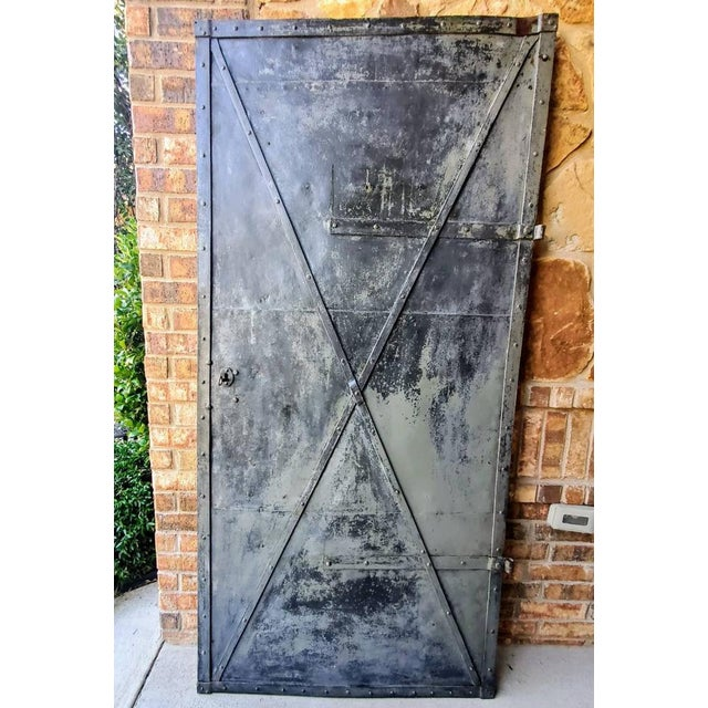 A strong, patinated antique iron cellar door from the mid 19th century. Rustic, primitive, and substantial but not...