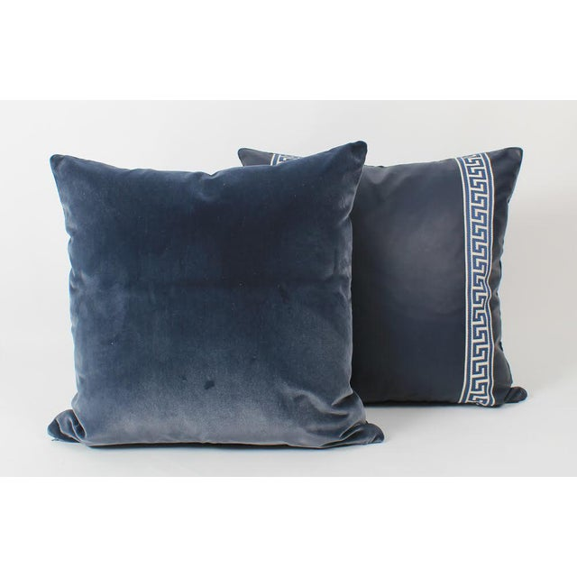 Pair of custom pillows in navy blue leather with coordinating navy-and-ivory Greek key pattern tape on fronts....