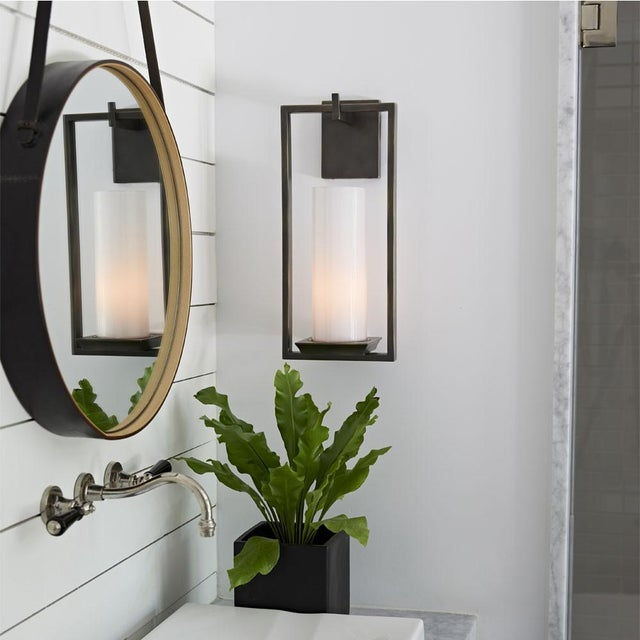 Arteriors round mirror with a black iron frame that is accented with brushed brass hardware. The mirror hangs from a black...
