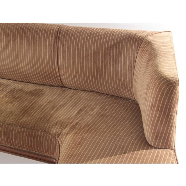 An L shaped Italian upholstered sofa having brass caps on the feet and a wood border circa 1960.