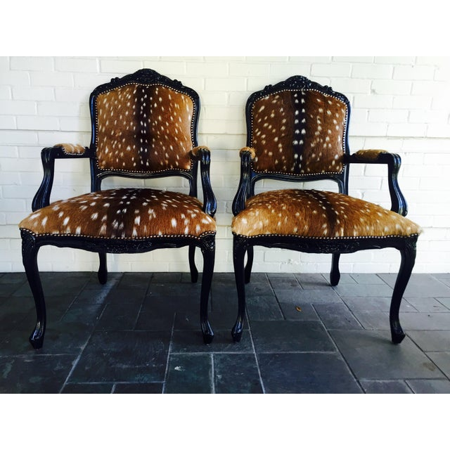 "Gorgeous pair of Axis or ""antelope"" French arm chairs. These amazing chairs have been lacquered in jet black, decorated..."