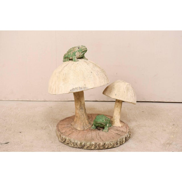 A whimsical midcentury garden sculpture depicting a pair of mushrooms and frogs atop a faux bois slab base. This folk art...