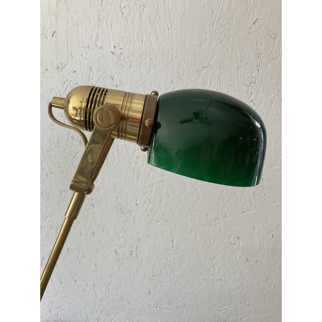 A solid brass adjustable table lamp with a dark green glass domed bulb cover. In excellent working condition.