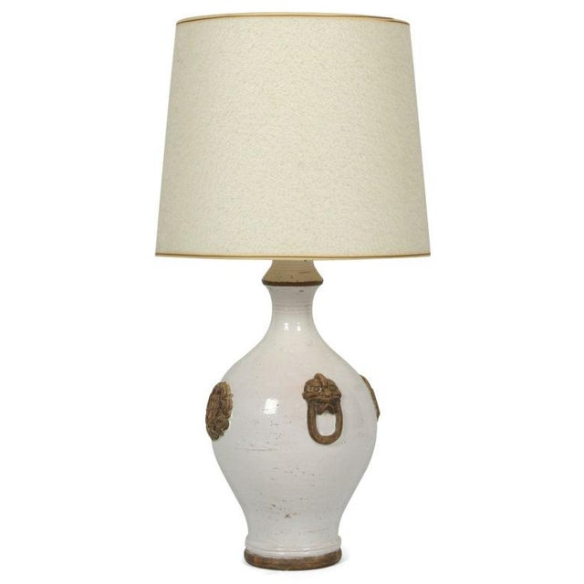 A fine ceramic table lamp in an ovoid form with a double waisted flared neck and flanked on four sides by animal masks...