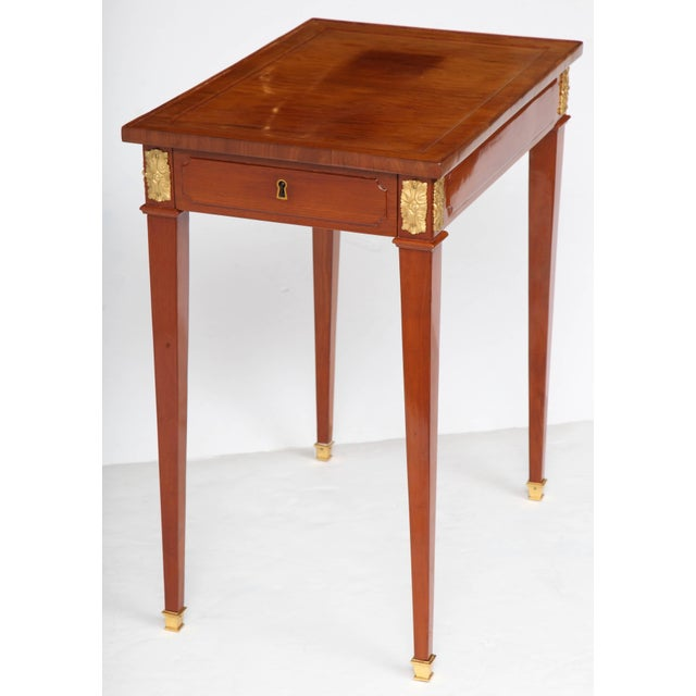 A Louis XVI period ormolu-mounted writing table with a drawer on one end and a writing slide on the other, raised on...
