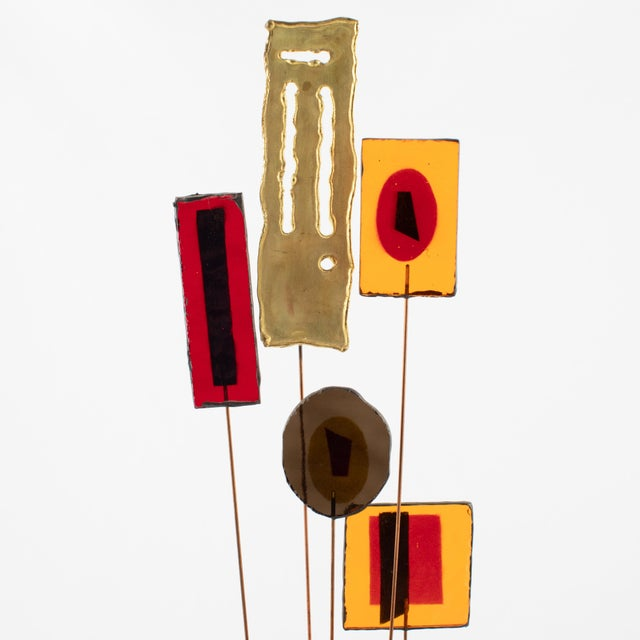 Tabletop sculpture features colorful resin disks and rectangles along with torch-cut brass rectangles supported by copper...