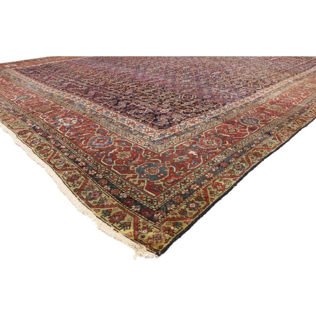 This hand knotted wool distressed antique mahal area rug features an all-over geometric floral pattern known as the Herati...