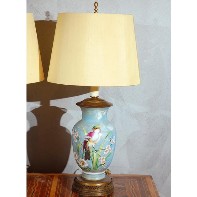 "A nice pair of decorated blue glass table lamps. They show birds and flowers painted on. England :circa 1910's 34"" H X6"" W..."