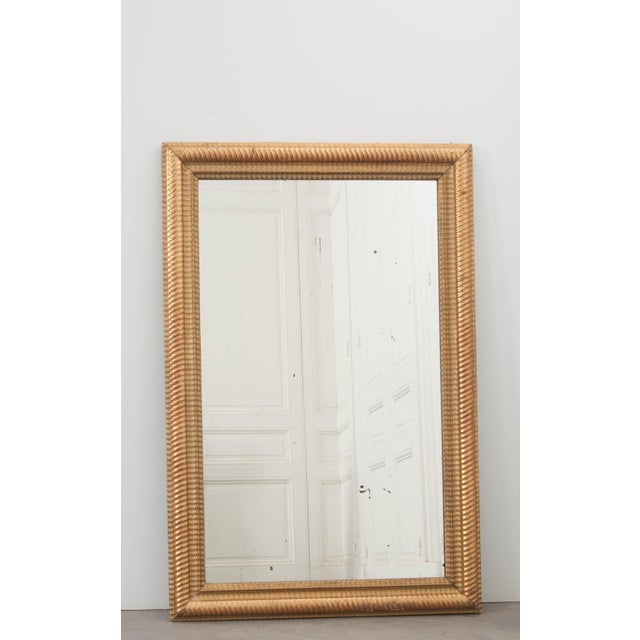 A spectacular gold gilt mirror with wonderful wavy, ribbed frame from 19th century, France. The mirror retains its...