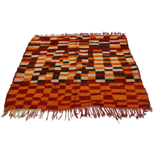 A vintage hand-knotted Moroccan wool rug featuring an ornate checkerboard pattern. Rendered in red, orange, charcoal,...