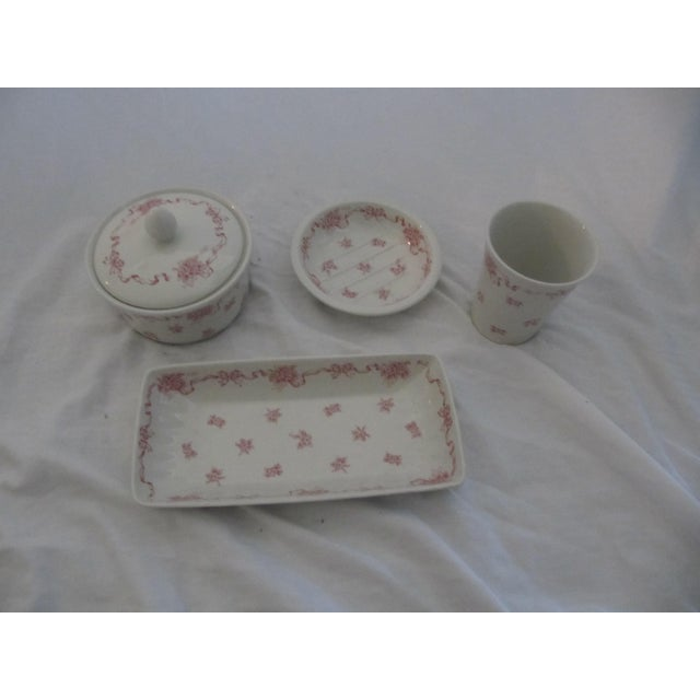 This is a four piece china bathroom accessory set by Laura Ashley in the pink Ribbons design. It consists of the cotton...