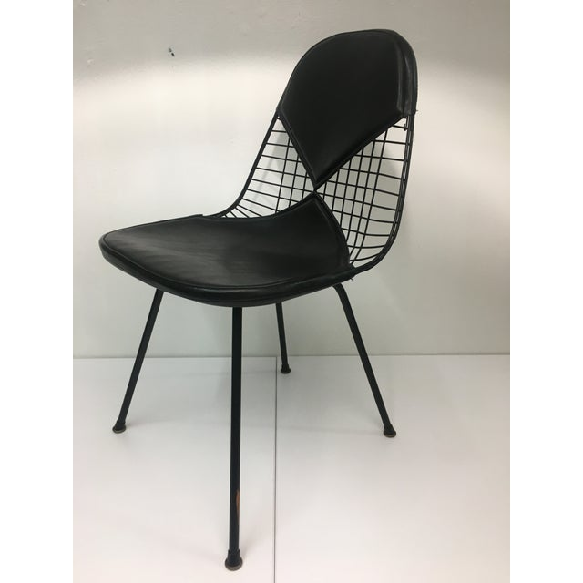 Authentic from the mid-century era, this classic Eames chair features powder-coated black wire seat on the iconic black...