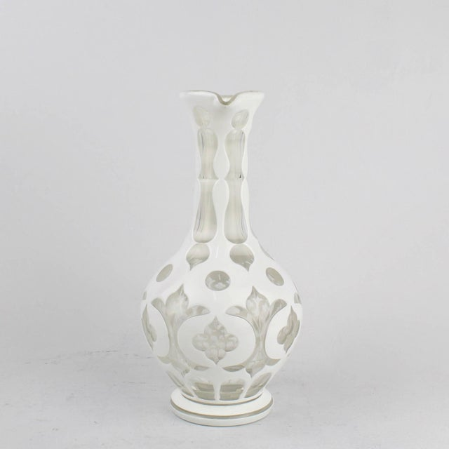 A fine example of a Bohemian overlay glass pitcher or ewer. The pitcher has an elongated neck, applied handle and an...