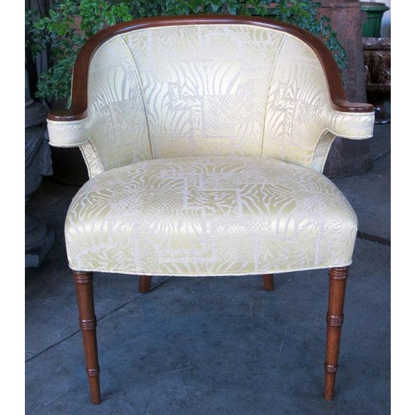 A shapely pair of English regency-inspired mahogany salon chairs; each with gracefully arched crest sloping to the...