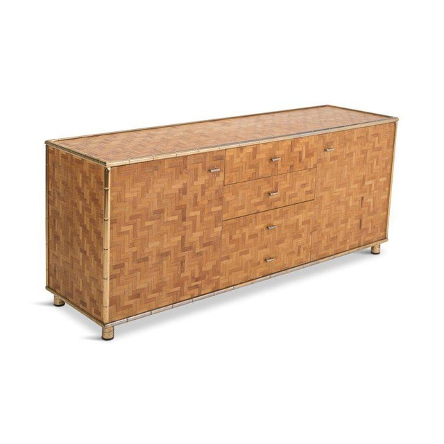 Rattan cladded sideboard with brass bamboo shaped edges, giving this item a very warm (almost tropical) appearance. In...
