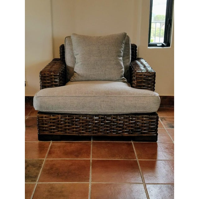 This wonderful and comfortable chair is made of finely woven wood and recently reupholstered in a grey chenille fabric....