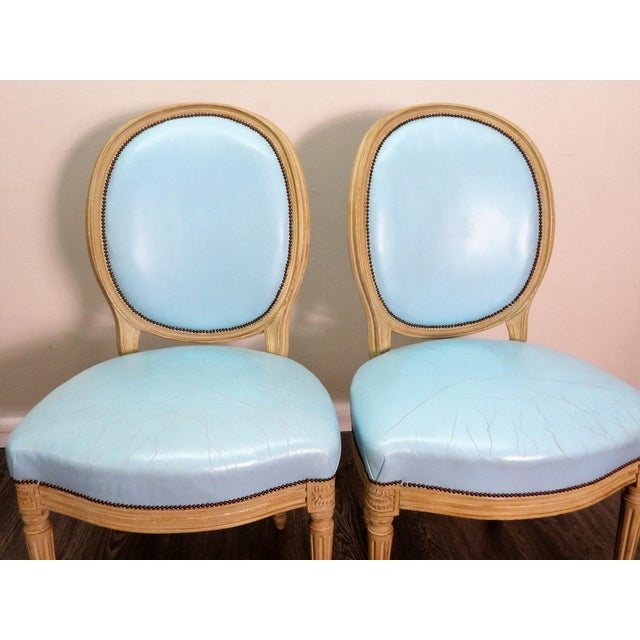A pair of Balloon Back Chairs. This vintage pair feature turned legs with elegant curved woodwork, leather upholstery with...