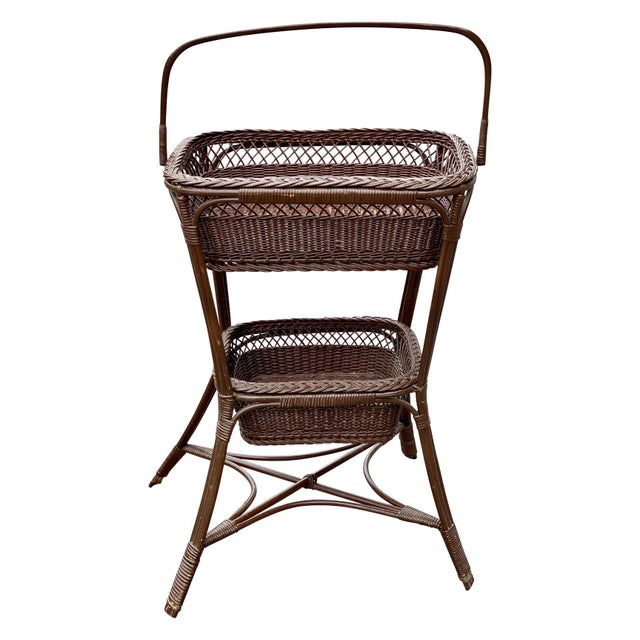 An unusually designed Victorian Wicker Basket Sewing Stand from the Mid 20th Century. This complete rattan and lacquered...