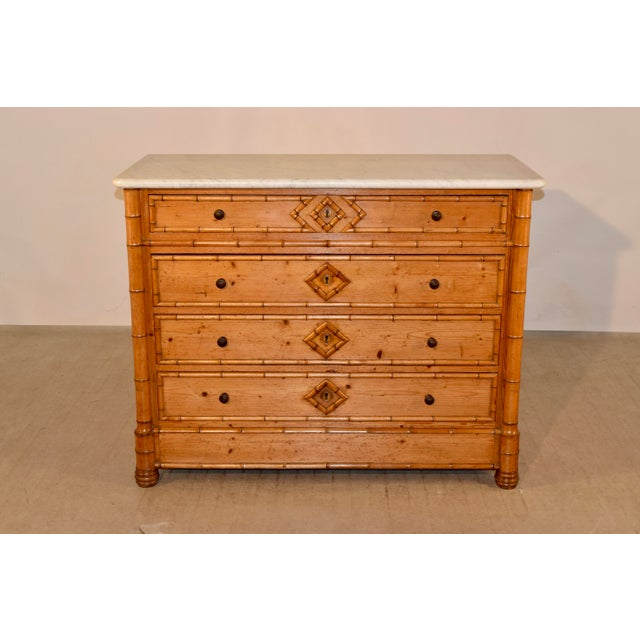 19th century faux bamboo chest of drawers made from cherry and pine. The top is Carrara marble, and follows down to simple...