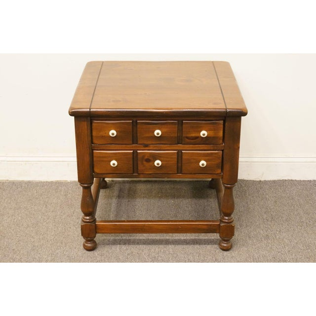 This is a vintage Ethan Allen nightstand made of antiqued pine wood. The piece is from the late 20th century.