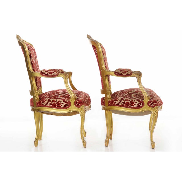 This striking pair of Louis XV style fauteuils retain an original and rather early gilding naturally worn down to the...