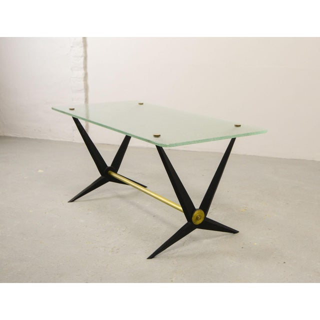 Mid-century Italian design coffee / side table designed by Angelo Ostuni in the 1950s. The black metal scissor base...