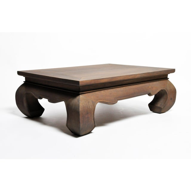 A contemporary Thai Lanna coffee table with large leg supports, freshly carved from teak. Recently refinished color.